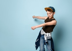 Naughty boy in stylish cap jumping in place looking down under feet with roguish smile. Childhood, sly kid, troublemaker. Three quarter length portrait isolated on blue background. Copy space