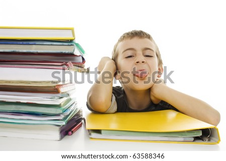Naughty child sticks out his tongue with school books on the table