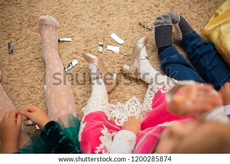 Naughty children are tired and sit on the floor and watch cartoons. Legs of children close up.