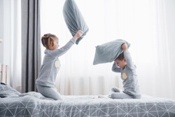 Naughty children Little boy and girl staged a pillow fight on the bed in the bedroom. They like that kind of game.