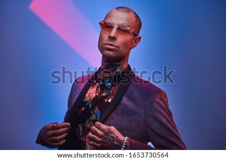 Naughty, daring, tattooed, bald male model posing in a studio for the photoshoot wearing fashionable custom made grey tuxedo, red glasses, jewelery and rose patterned shirt, fashion style ストックフォト ©