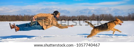 Naughty dog knocked pulls the master off his feet on a leash. not listening orders. The owner and his pet friend are disobedient. dragging a man in the snow behind him. a naughty dog. does not listen.