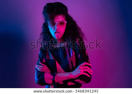 Naughty fashion young african american girl black woman wear stylish pink glasses arms crossed show tongue look at camera isolated on party purple studio background, portrait, copy space