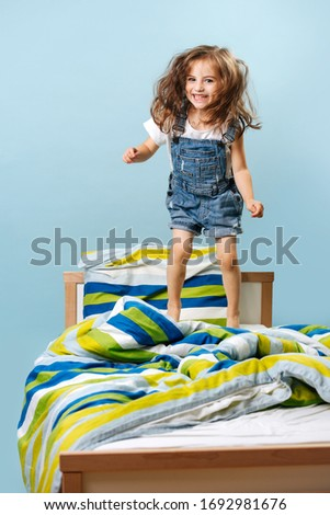 Naughty funny girl - toddler does not want to sleep, she jumps on the bed in a denim jumpsuit on a blue background