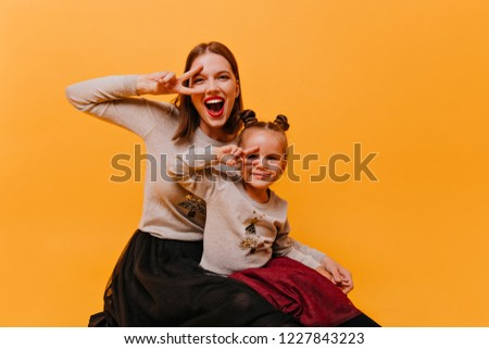 Naughty, joyful, happy mother with her little daughter in identical New Year sweater sit on the floor and show a sign of peace. photo of young and little girls on orange background looking into camera