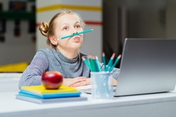 Naughty little blond girls, pupil of elementery school holding pencil like mustache sits on desk at classroom. Bored kid doing homework or sitting on boring school lesson. Tired and sad student girl.