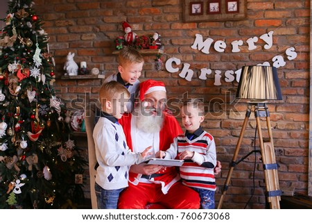 Naughty male children of European appearance want Christmas grandfather to show them interesting cartoons on gadget in decorated room with high floor lamp, walls which posters hang, and tree dressed
