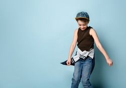 Naughty schoolboy in stylish cap jumping in place looking down under feet with roguish smile. Childhood, sly kid, troublemaker. Three quarter length portrait isolated on blue background. Copy space
