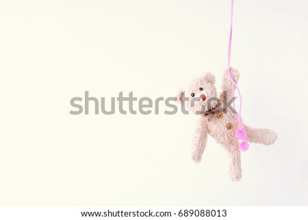 Naughty teddy bear is hanging on the pink line,Everywhere the teddy bear is happy
