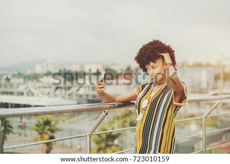 Naughty young black girl with curly afro hair in traditional suit is being goofy while making selfie near railing of the roof on bright summer day  with cityscape and palms in blurred background