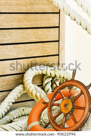 Nautical background, marine travel with adventure collection - sea wheel, ropes, lifebuoy and wooden plank on a white yacht. Ship interior with ropes. Mooring rope turns at the yacht on deck.