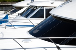 Nautical background of a row of luxury yachts, with black tinted windows and chrome metal railings on white fiber glass bows