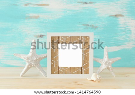 Nautical concept with empty photo frame and starfish over wooden table. For photography montage
