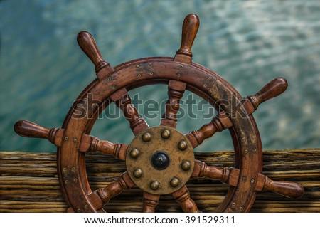 Nautical Detail Of A Ship\'s Wheel Against Tropical Ocean Water