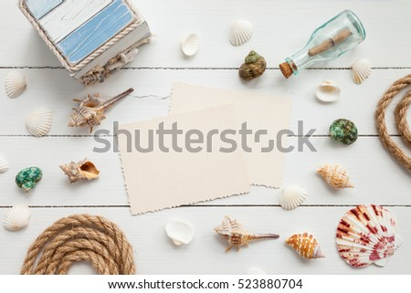 Nautical life style items: bottle with message, sea shells, chest, rope and old empty photo for the inside. Marine concept.