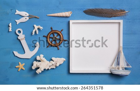 Nautical maritime decoration with anchor, sailboat and a white sign on a blue wooden background. Idea for summer vacation concepts.