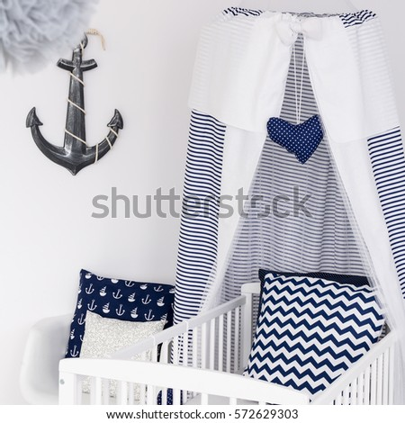 Nautical themed nursery for boy or girl with baby cot with patterned pillows #572629303