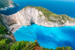 Navagio beach from top at Zakynthos island, Greece. Stranded shipwreck in unique beautiful blue bay surrounded by limestone mountain walls