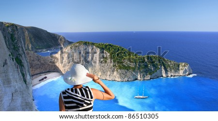 Navagio beach with woman on cliff, Zakynthos, Greece