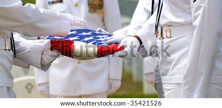 Naval Honor Guard folding US Flag over casket during funeral at Arlington National Cemetery