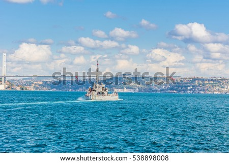 Naval vessel passing though Bosphorus  Bridge with background of Bosphorus strait on a sunny day with background cloudy blue sky and blue sea in Istanbul, Turkey. Blue Turkey concept.