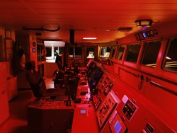 Navigation bridge on nautical maritime merchant vessel at the night with red night light at anchor