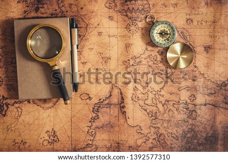 Navigation Explore of Journey Planning., Travel Destination and Expedition Plan Vacation trip., Close Up of Layout Magnifying Glass, Compass and Note Book on The World Map Background. #1392577310