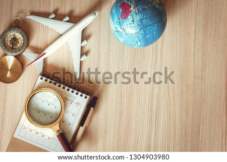 Navigation explore of journey planning., Travel destination and expedition plan vacation trip., Top view of layout magnifying glass, calendar, compass, airplane model and global model on the table.