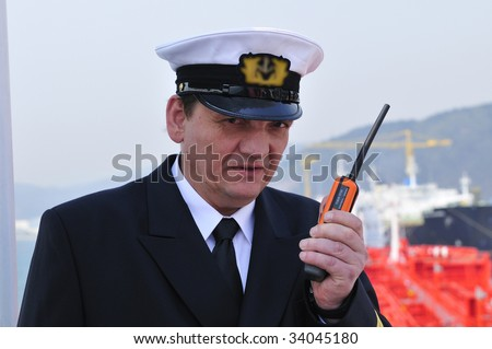 Navigation officer is talking by VHF radio, looking ahead on the navigation bridge of ocean ship