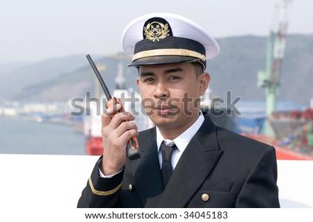 Navigation officer is talking by VHF radio, looking ahead on the navigation bridge of ocean ship