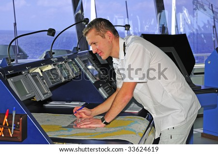 Navigation officer manages devices, looking ahead on the navigation bridge of ocean ship
