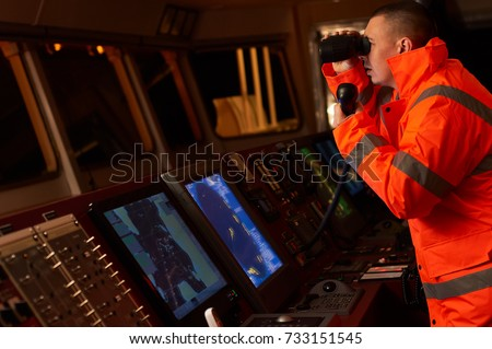 Navigation officer / Pilot on bridge of a vessel underway with radio station and binocular in hands Сток-фото ©