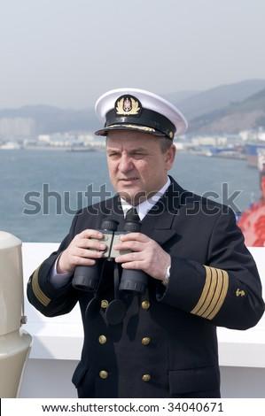 Navigation officer with binocular, looking ahead on the navigation bridge of ocean ship