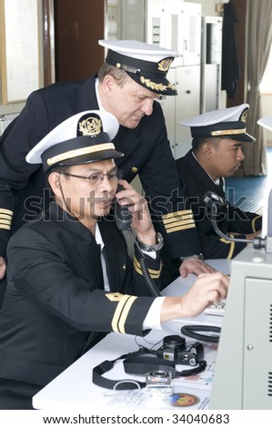Navigation officers manage devices, looking ahead on the navigation bridge of ocean ship