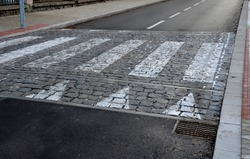 navigation tactile tiles strip for blind and disabled pedestrians who have vision problems. The red pavement has protrusions that lead the person to the crossing and draw attention to the edge road