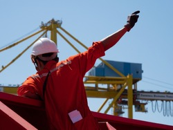 Navigational deck officer giving signals during mooring operation with a gantry crane in the background.