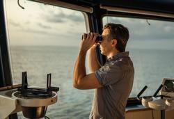 Navigational officer lookout on navigation watch looking through binoculars. Marine industry.  collision regulations