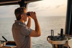 Navigational officer lookout on navigation watch looking through binoculars. Marine industry. COLREG collision regulations