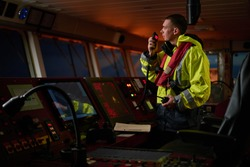 Navigator, pilot, captain part of ship crew performing daily duties with VHF radio, binoculars, logbook, standing nearby to ECDIS and radar station on board of modern ship with high quality equipment