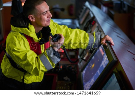 Navigator, pilot, captain part of ship crew performing daily duties with VHF radio, binoculars, logbook, standing nearby to ECDIS and radar station on board of modern ship with high quality equipment Сток-фото ©