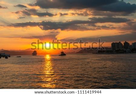 Navio de carga saindo do porto, navegando para o alto mar com um lindo por do sol Foto stock ©
