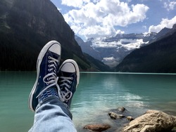 Navy blue Chuck Tylor Converse All-Star sneakers resting rocky shoreline of glacier-fed aqua green Lake Louise with the glacier filled Canadian Rockies, framing a cloud filled blue sky.