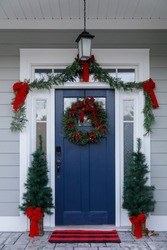 Navy blue front door of contemporary new construction siding gray home decorated for Christmas holidays with wreath trees and garland