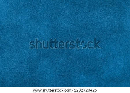 Navy blue matte background of suede fabric, closeup. Velvet texture of seamless turquoise leather. Felt material macro.