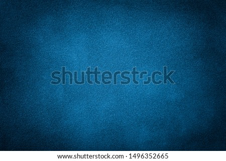 Navy blue matte background of suede fabric, closeup. Velvet texture of seamless turquoise leather. Felt material macro with dark vignette.