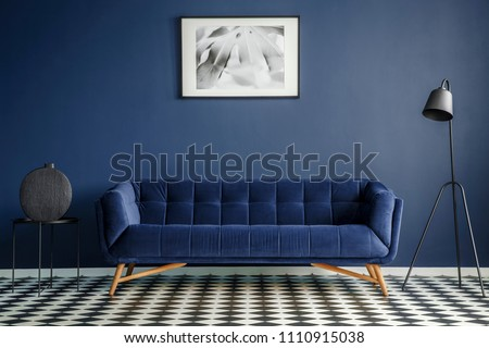 Navy blue room interior with comfortable plush couch in the middle, black lamp and side table with decoration standing on chessboard floor. Framed image on the wall. Real photo #1110915038