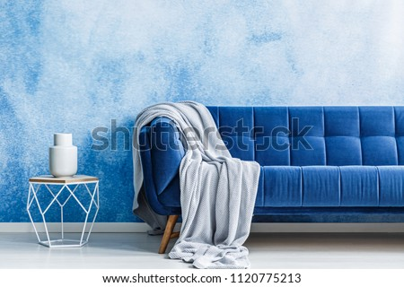 Navy blue sofa with gray blanket and openwork metal side table with a dish on top against watercolor, ombre wall in a modern living room interior. Real photo.