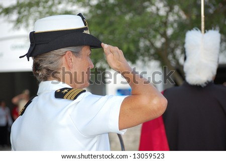 Navy Commander saluting flag at Memorial Day ceremony