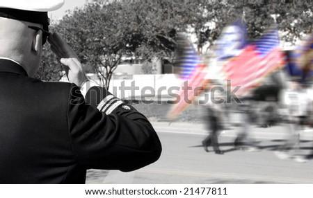 Navy officer saluting veterans in parade