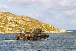 Navy ship in the rocky archipelago with sailors on deck